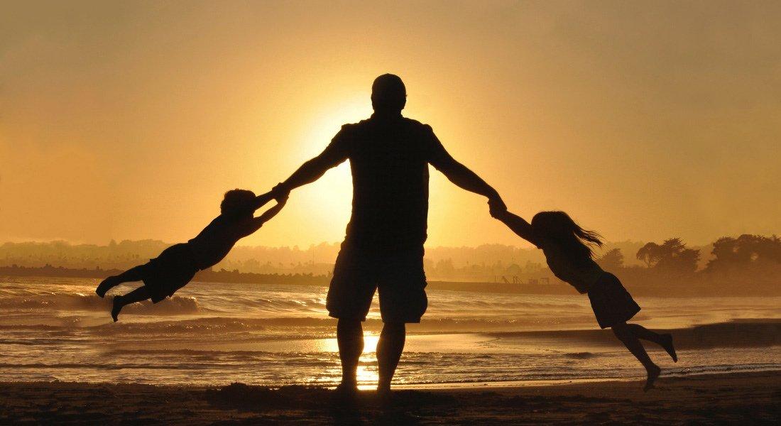 Un père et ses enfants devant un coucher de soleil